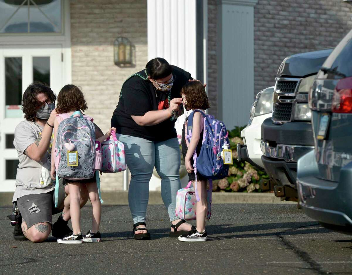 Ian Copland, left, and Megan Tucker, of Danbury, adjust their twin daughters Lilith, left, and Lydia Copland masks while dropping them off for the first day of kindergarten at the Danbury Primary Center in Brookfield. Monday, August 30, 2021, Brookfield, Conn.