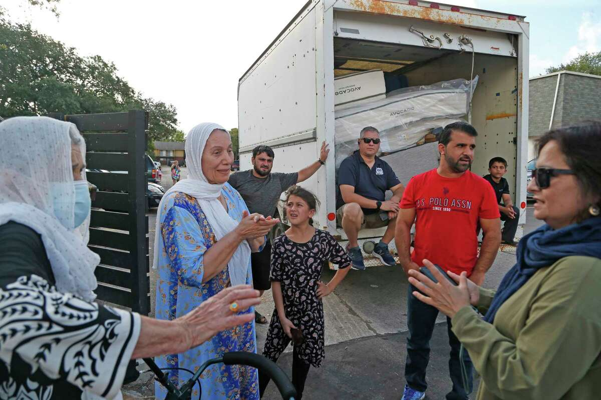 VetStrong founder and Afghanistan veteran James Pobanz, back center, waits on the truck as Iraw refugee Buzdan Farhan, second from left, tells Farhana Khan, right, where her apartment is located at Wurzbach Manor apartments on Saturday, Aug. 28, 2021.