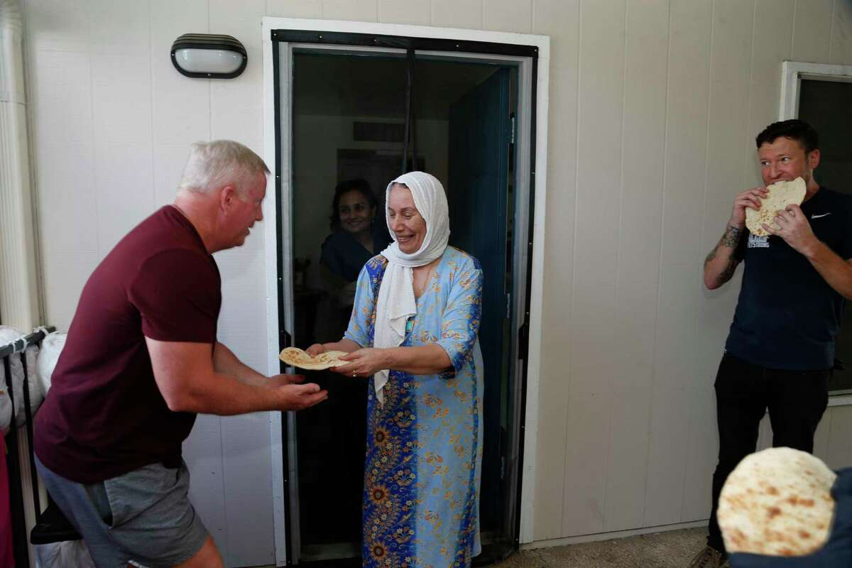 Iraq refugee Buzdan Farhan thanks veterans who moved a bed into her apartment by offering them bread at the Wurzbach Manor apartments on Saturday, Aug. 28,2021. On the left is volunteer Minder Huff. ASt right is veteran Erwin Frantti.