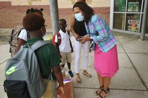 Principal Sangeeta Bella greets returning students on the first day of school at Discovery Magnet Elementary School in Bridgeport, Conn. on Monday, August 30, 2021.