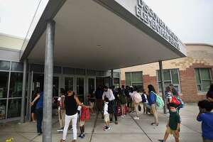 Students and parents wait for doors to open on the first day of school at Discovery Magnet Elementary School in Bridgeport, Conn. on Monday, August 30, 2021.
