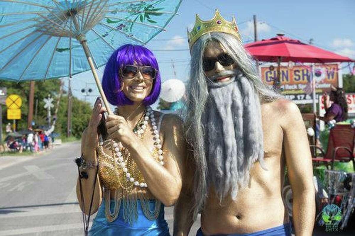 A couple dressed as mermaids march in the 2019 Mermaid Promenade in San Marcos.