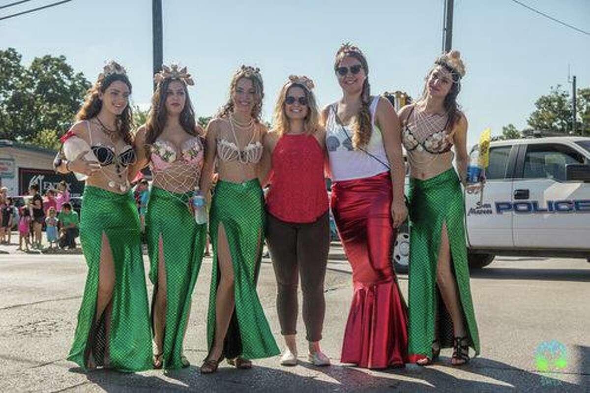 A group of women dressed as mermaids march in the 2019 Mermaid Promenade in downtown San Marcos.