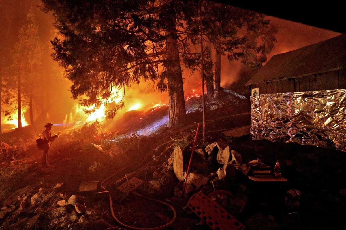 A firefighter monitors a back burn along Highway 50 next to a home that was partially wrapped in foil as crews continued structure prevention at the Caldor Fire in Strawberry, Calif.