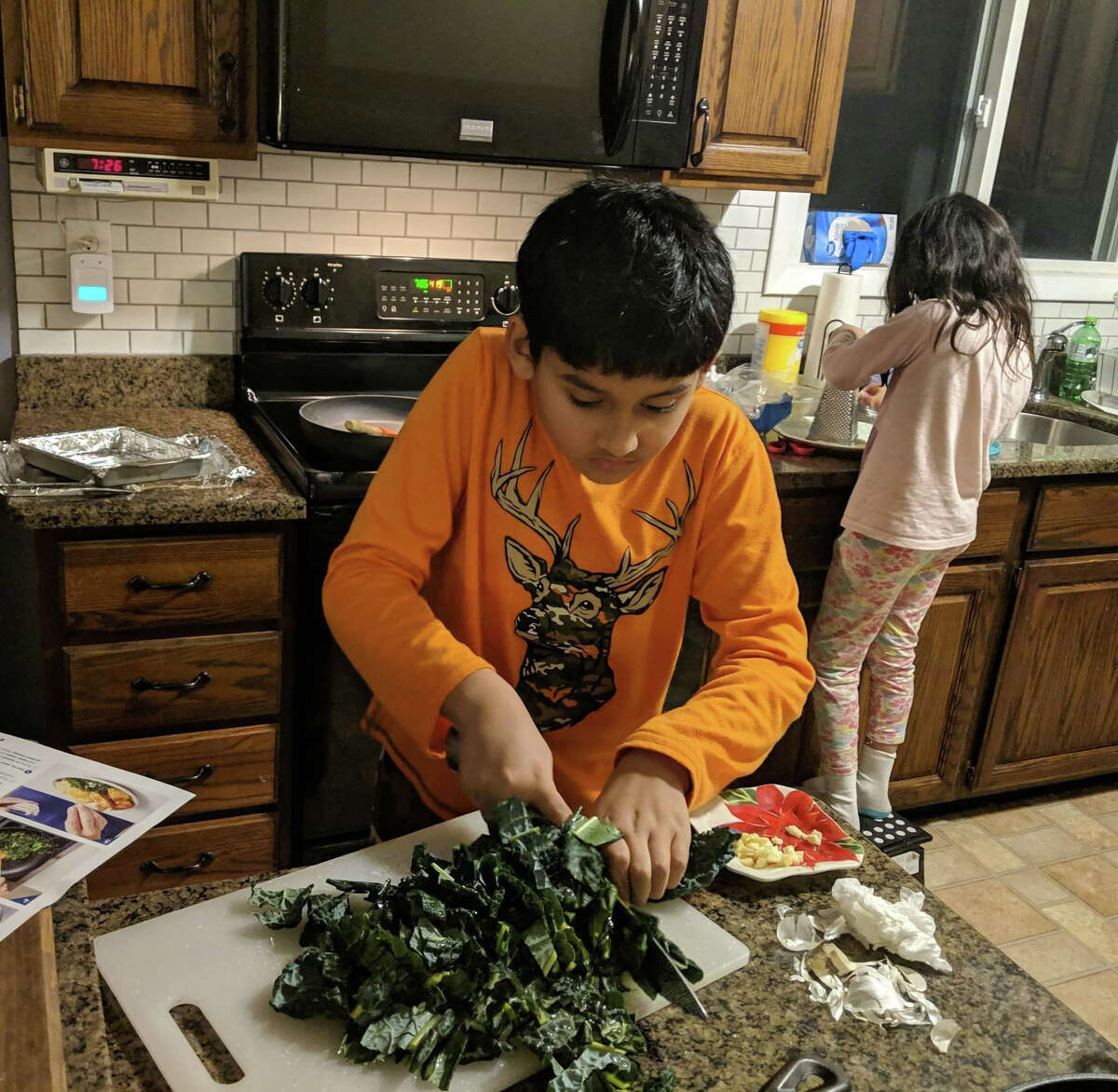 Angad Seshadri, foreground, and sister Nupur Seshadri prepare vegetables for dinner at their home in Latham. The children's mother, Nandini Seshadri, will be packing their school lunches to better monitor the nutritional content of their midday meals.