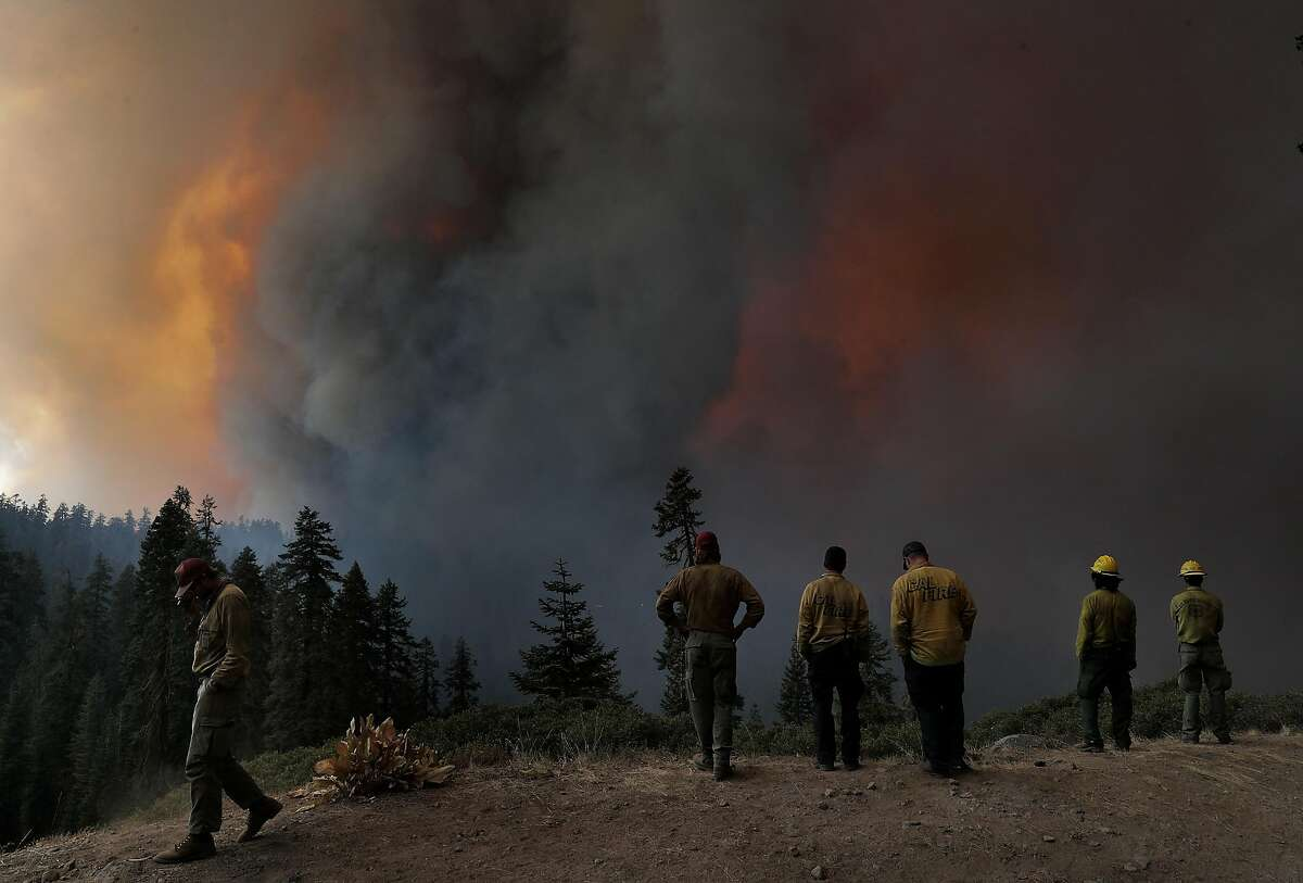 Firefighters monitor the advancing fire as it approaches Mormon Emigrant Trail near Hwy 88 outside Shingleton Springs, Calif., on Sunday, August 29, 2021.