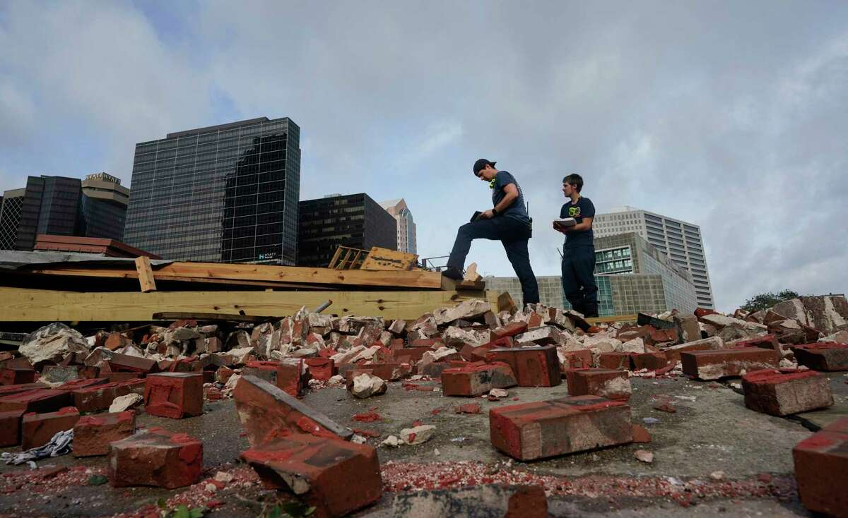 New Orleans Firefighters assess damage as they look through debris after a building collapsed from the effects of Hurricane Ida, Monday, Aug. 30, 2021, in New Orleans, La. All of New Orleans lost power right around sunset Sunday as the hurricane blew ashore on the 16th anniversary of Katrina, leading to an uneasy night of pouring rain and howling wind. The weather died down shortly before dawn. (AP Photo/Eric Gay)
