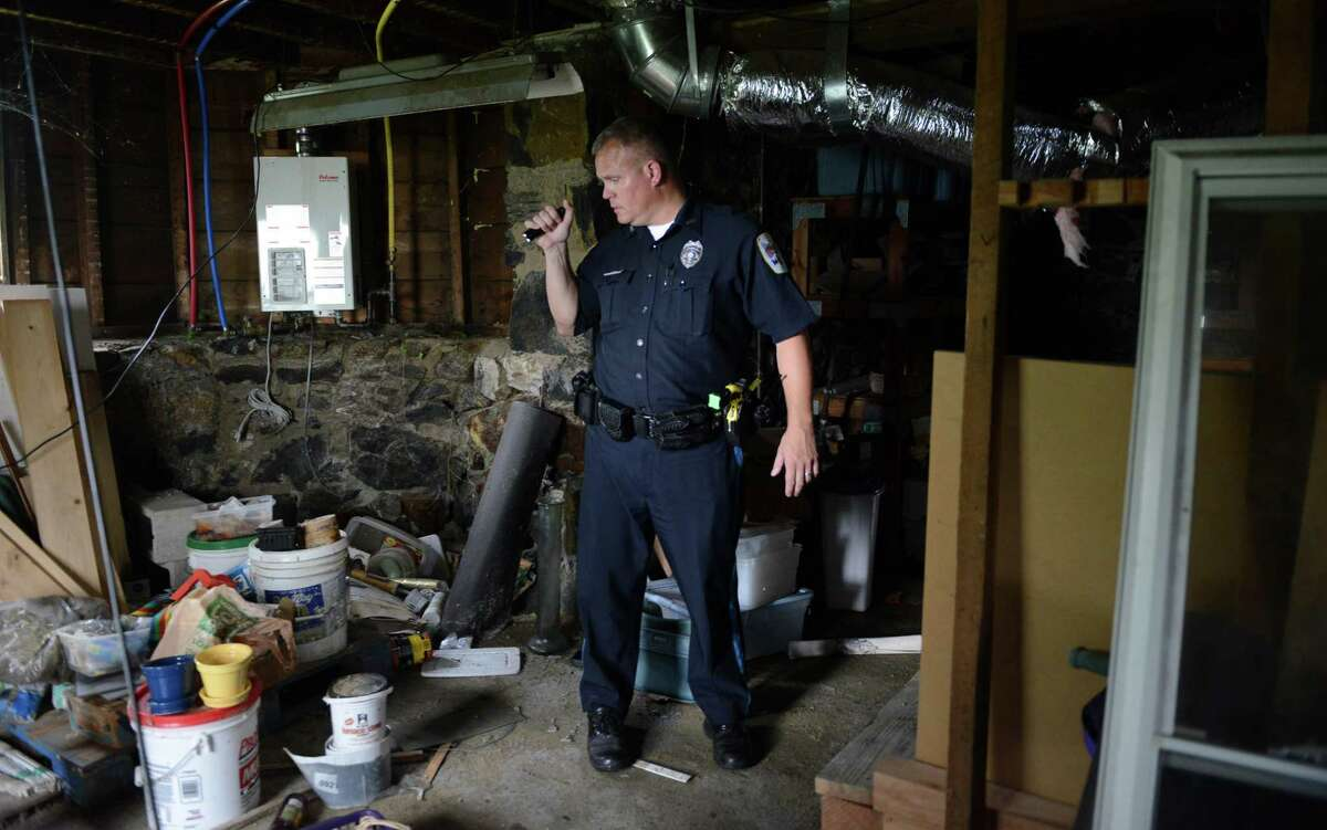 Danbury police officer Ken Utter, of Danbury's Unified Neighborhood Inspection Team (UNIT) checks out an abandoned property on Morris Street Tuesday, July 15, 2014. Utter was suspended for eight days following an internal investigation of an June 2021 incident at Danbury Library. This was the first time he was disciplined in his 25-year career with Danbury Police Department.