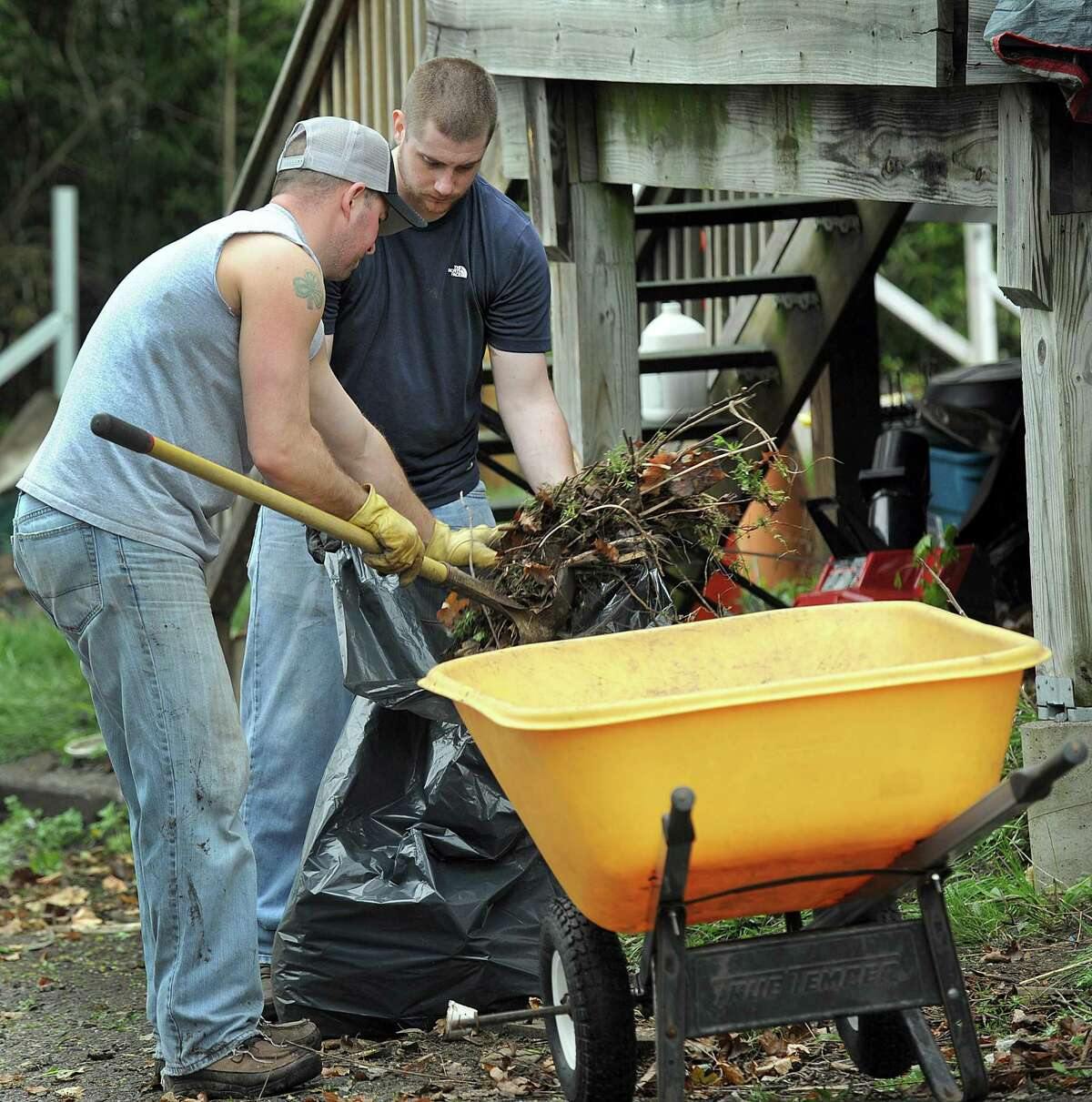 Ryan Howley, 31, left, and Chris Dennis, 26, both Danbury Police officers, volunteer to clean up the outside of Heidi Palmer's Danbury home Thursday, April 27, 2017. Dennis was required to take counseling and remedial training following an internal investigation of an June 2021 incident at Danbury Library.
