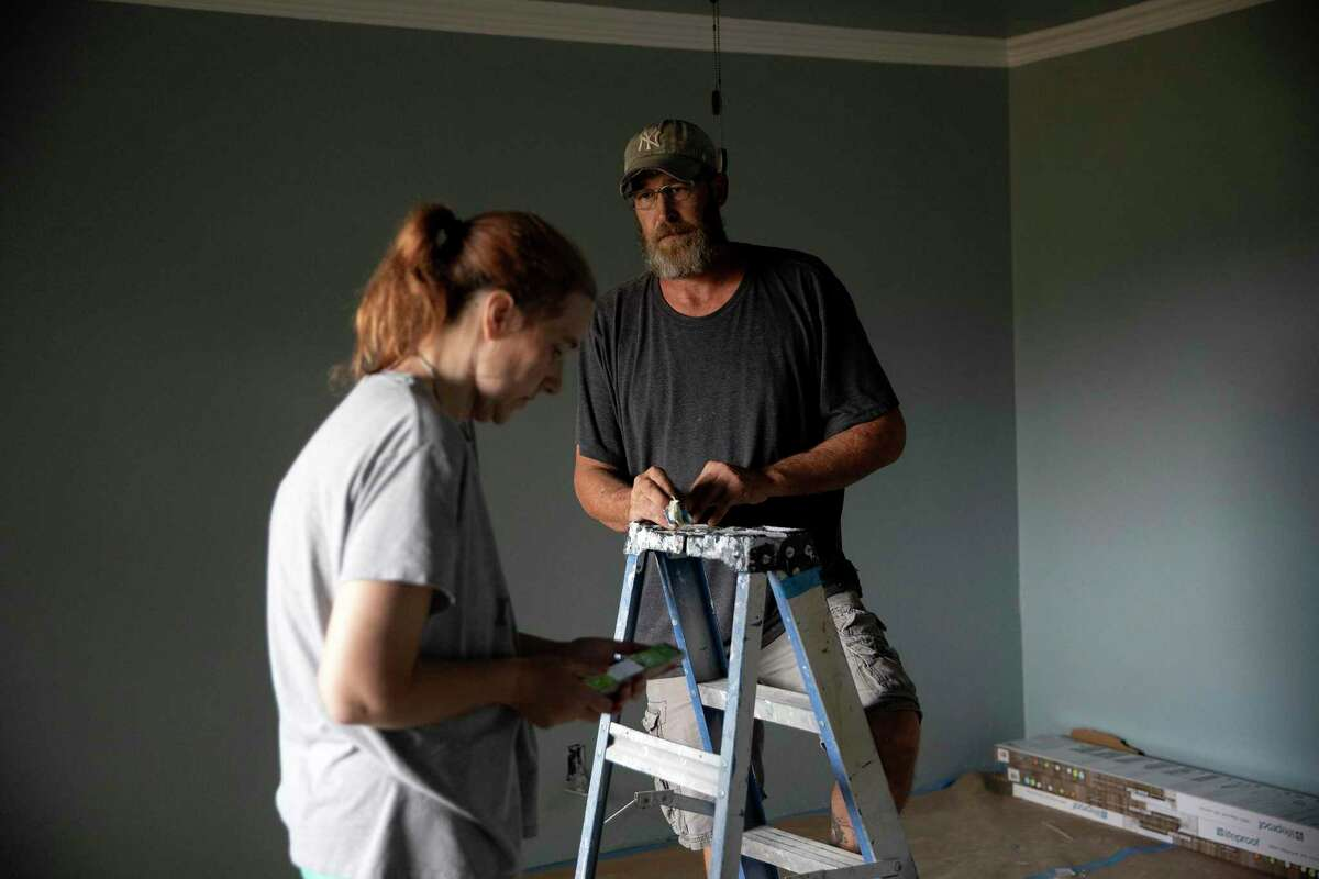 James and Ann Creasman survey the work of the contractors in one of the back bedrooms they are hoping to move back into in a couples days time.