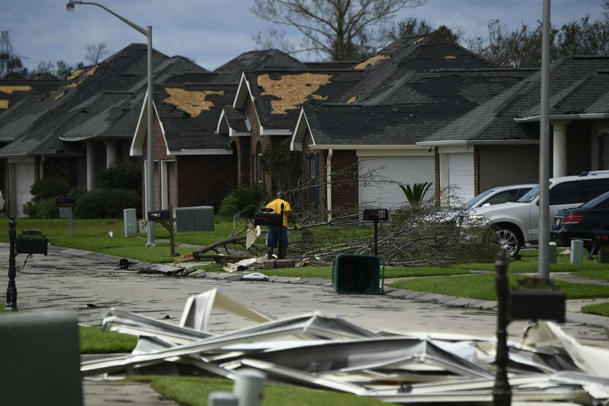 A person picks up debris damage near their home in Laplace, Louisiana, on August 30, 2021 after Hurricane Ida made landfall. - Powerful Hurricane Ida battered the southern US state of Louisiana, leaving at least one dead and knocking out power for more than a million people, including the whole of New Orleans. Ida slammed into the Louisiana coast as a Category 4 storm on August 29, 2021, 16 years to the day after Hurricane Katrina devastated New Orleans, but had weakened to a tropical storm early August 30, 2021.The storm knocked out power for all of New Orleans, with more than a million customers across Louisiana without power, according to outage tracker PowerOutage.US. (Photo by Patrick T. FALLON / AFP) (Photo by PATRICK T. FALLON/AFP via Getty Images)