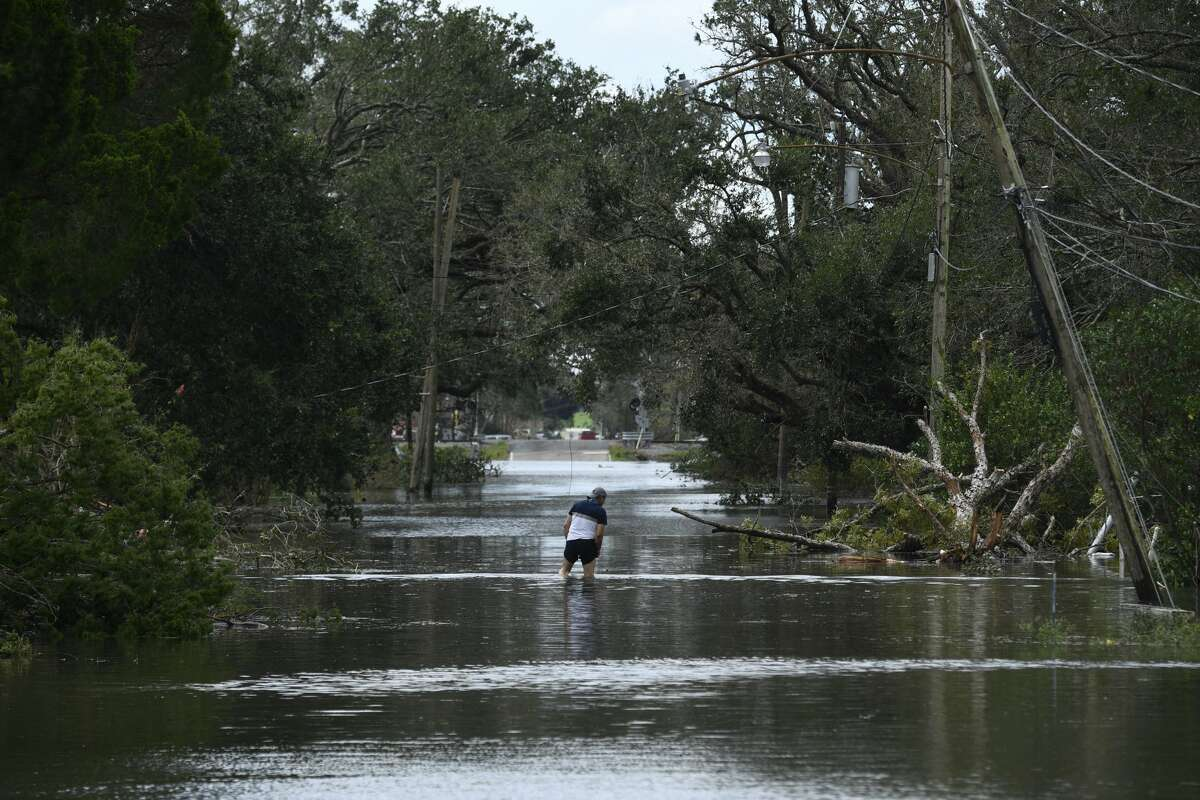 A person wades through flood waters in Norco, Louisiana, on August 30, 2021 after Hurricane Ida made landfall. - Powerful Hurricane Ida battered the southern US state of Louisiana, leaving at least one dead and knocking out power for more than a million people, including the whole of New Orleans. Ida slammed into the Louisiana coast as a Category 4 storm on August 29, 2021, 16 years to the day after Hurricane Katrina devastated New Orleans, but had weakened to a tropical storm early August 30, 2021.The storm knocked out power for all of New Orleans, with more than a million customers across Louisiana without power, according to outage tracker PowerOutage.US. (Photo by Patrick T. FALLON / AFP) (Photo by PATRICK T. FALLON/AFP via Getty Images)