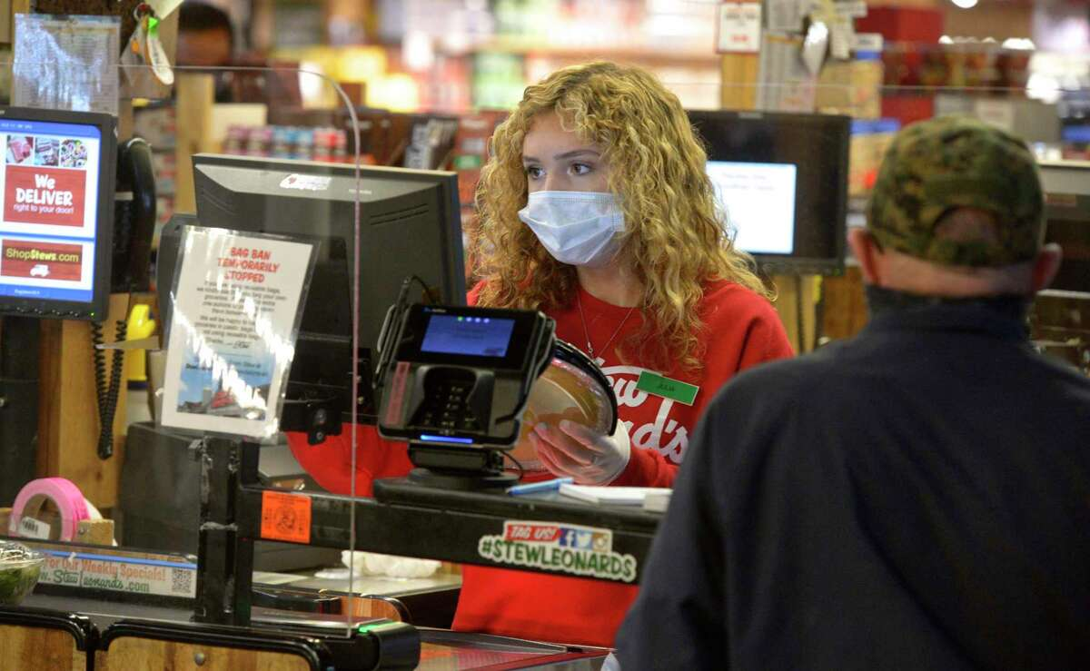 File photo. Julia Barnum of Newtown wears a mask while working at Stew Leonard's in Danbury, Conn. Tuesday, April 21, 2020. Newtown has imposed a mask mandate for indoor public spaces. Monday Aug. 30, 2021.