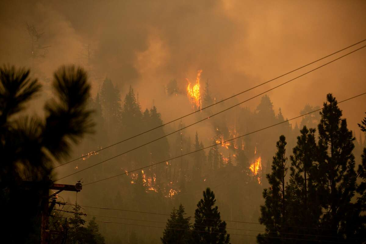 A spot fires burns on the ridge behind the historic Strawberry Lodge as firefighters continue to tackle the Caldor Fire as it creeping closer to South Lake Tahoe on Saturday, Aug. 28, 2021.