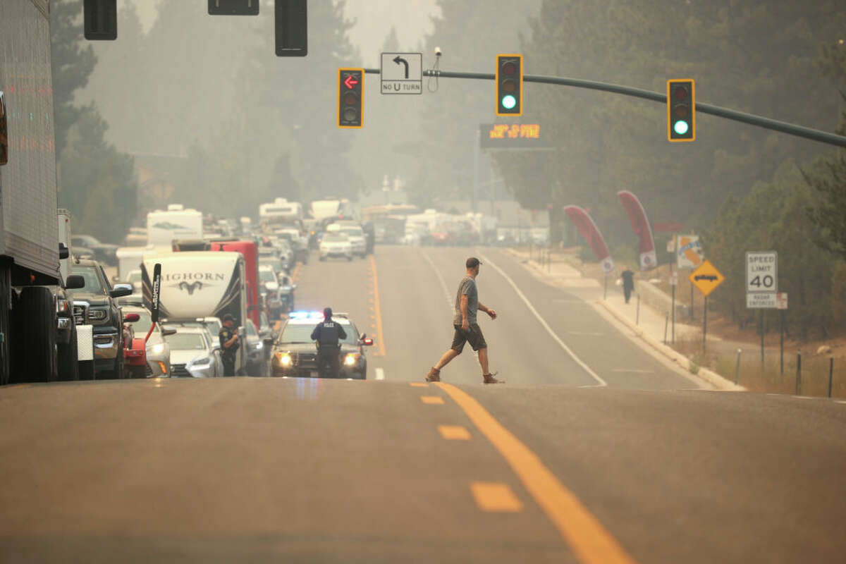 A pedestrian is passing by on Hwy 50 as traffic recedes as people exit before a Caldor fire in South Lake Tahoe on August 30, 2021.