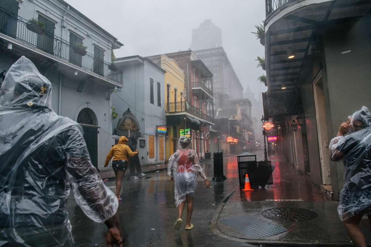 A group of people walk through the French District during Hurricane Ida on August 29, 2021 in New Orleans, Louisiana. (Photo by Brandon Bell/Getty Images)