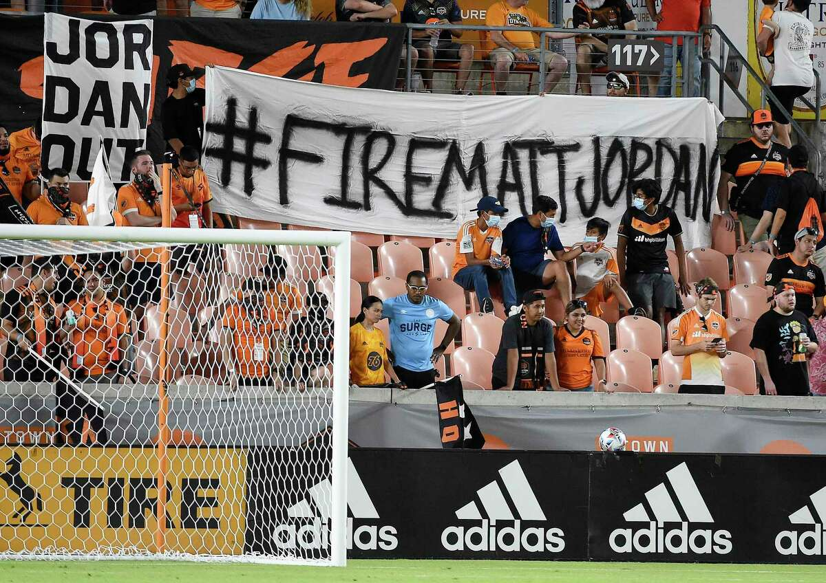 Fans hold signs calling for the firing go Houston Dynamo General Manager Matt Jordan during the second half of an MLS soccer matchv against FC Dallas, Saturday, Aug. 21, 2021, in Houston.