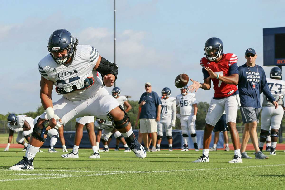 Ahofitu Maka, left, snaps the ball to Frank Harris during a UTSA football practice and scrimmage in the inaugural 'Runners at the Park event at the UTSA Park West Athletic Complex on Saturday, Aug. 17, 2019.