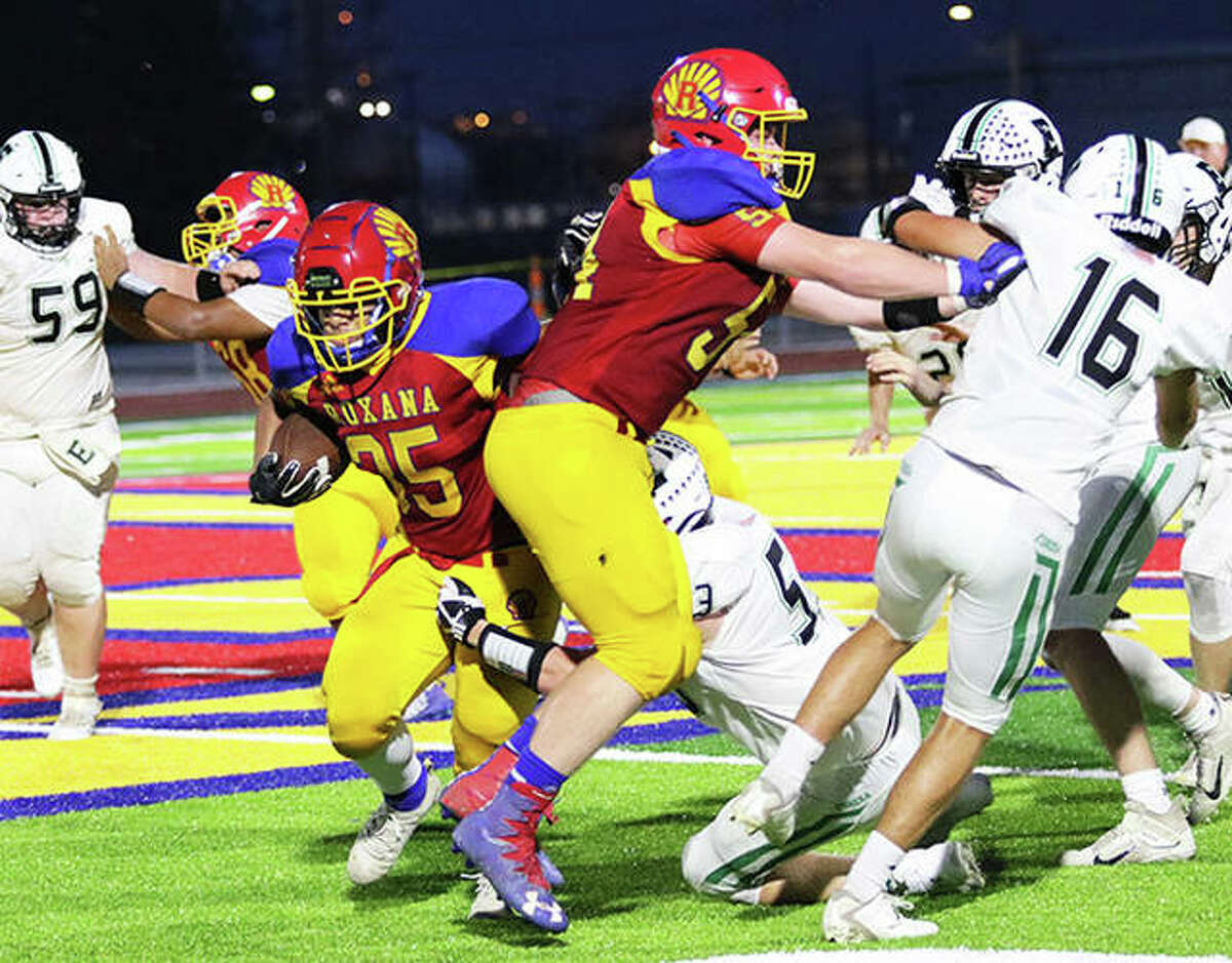 Roxana offensive lineman Kaden Bloemker clears Eureka defensive back Drew Dingledine (16) from the play while Shells RB Terrel Graves (35) runs through a tackle Friday night in Week 1 football action at Raich Field in Roxana.