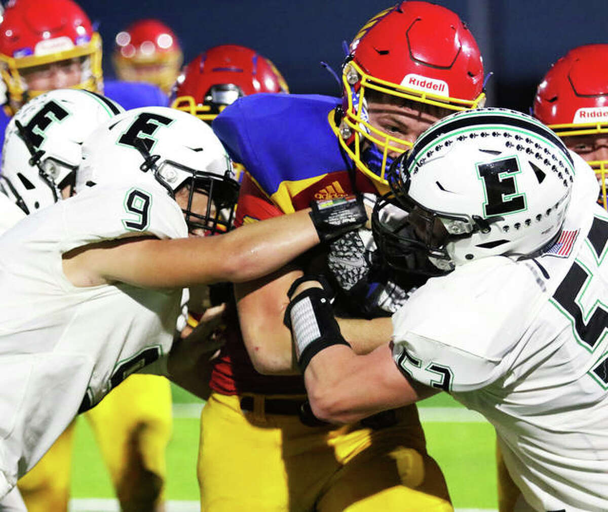Roxana RB Evan Wells (middle) secures the football while taking on Eureka defenders Friday night in Roxana. Wells rushed for 147 yards on 18 carries in the Shells' loss.