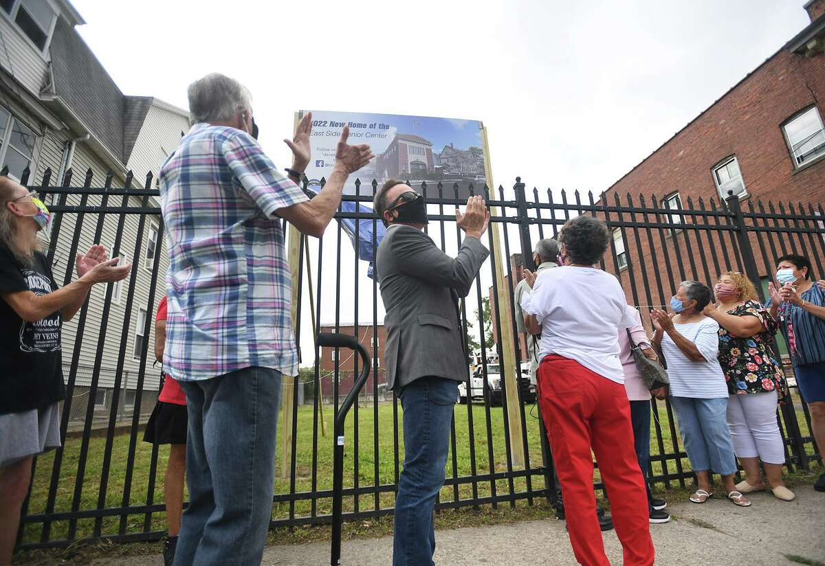 Bridgeport Mayor Joe Ganim, city council members, and neighborhood seniors applaud the unvailing of the new East Side Senior Center at the former Fire Engine Company 10 on Putnam Street in Bridgeport, Conn. on Monday, August 30, 2021.
