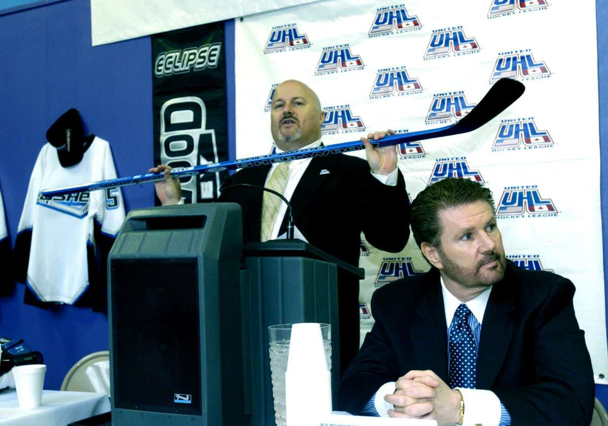 """In this file photo, United Hockey League president Richard Brosal holds a hockey stick during a news conference announcing the coming of professional hockey to Danbury. The Trashers, owned by James Galante, right, played at the Danbury Ice Arena. The Danbury Trashers are the subject of a new documentary, """"Untold: Crime and Penalties,"""" on Netflix."""