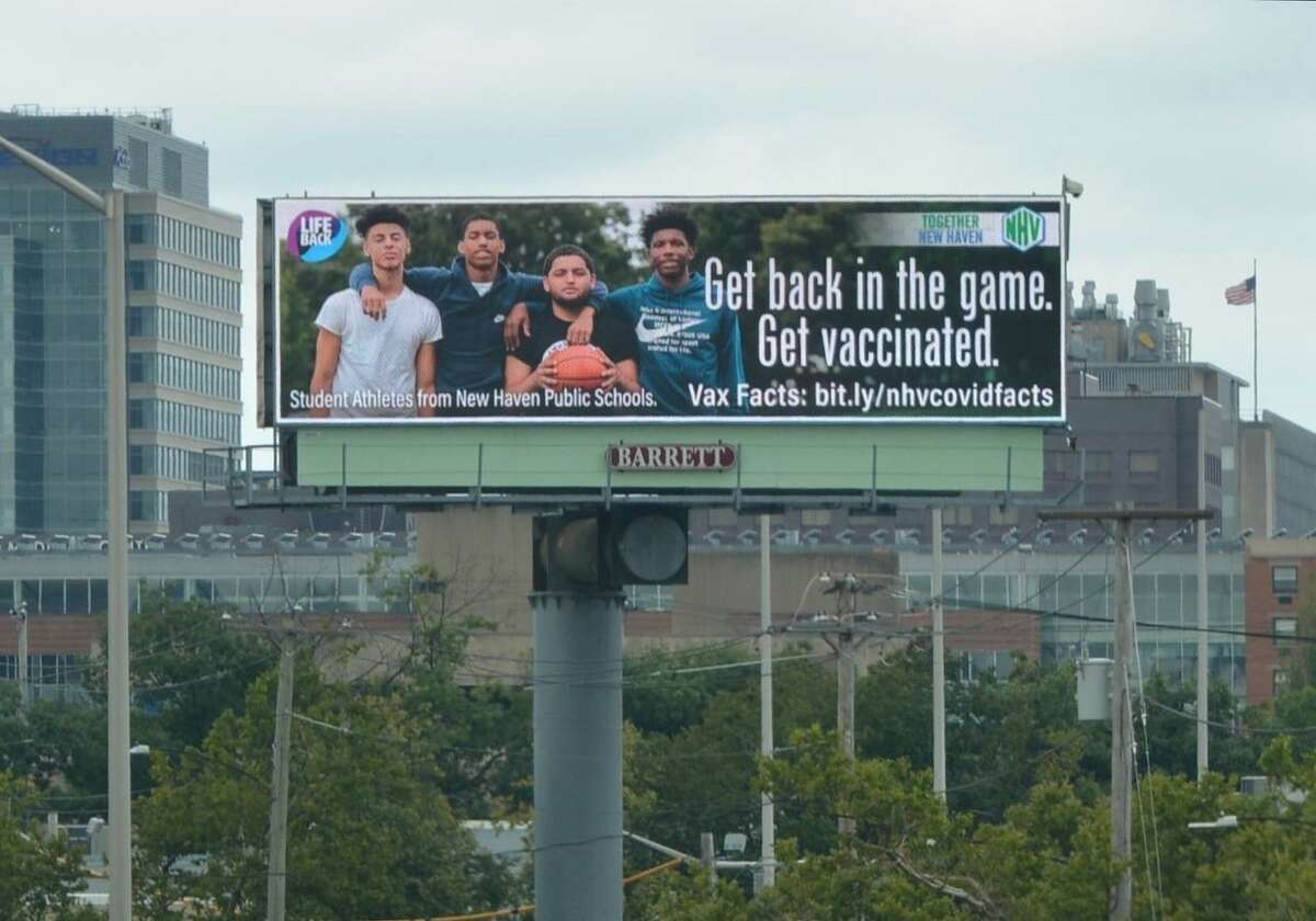 From left, Adam Elkharraz, Derrell Redd, Fredo Delgado and Christian McClease appear on a digital billboard in New Haven to promote getting the COVID-19 vaccine.
