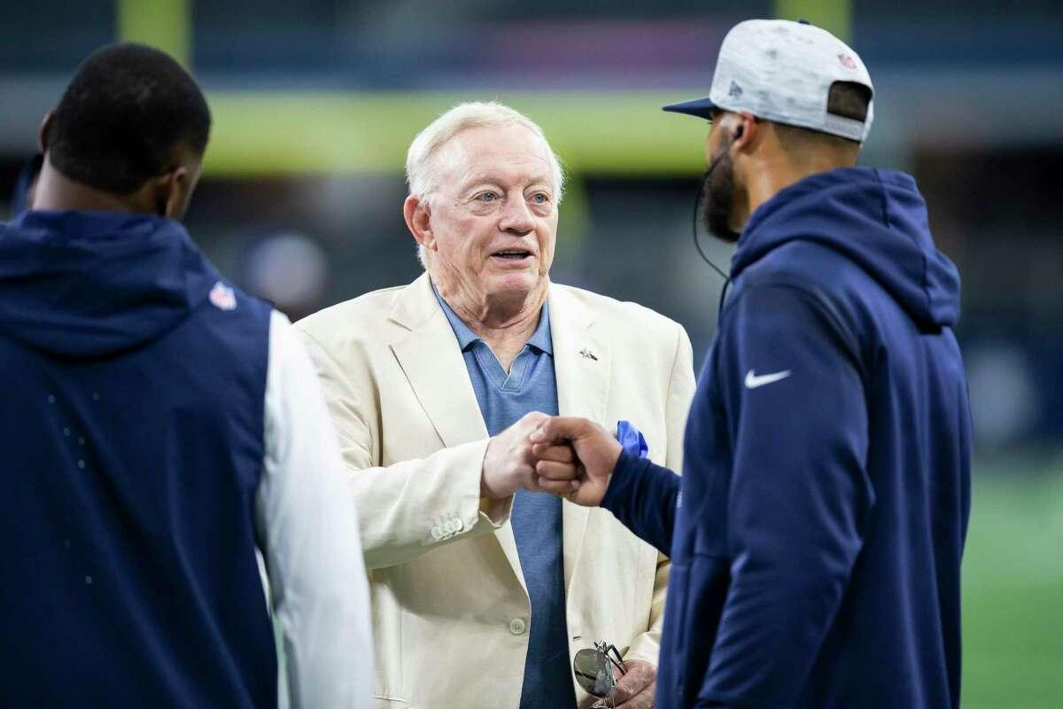 Dallas Cowboys owner Jerry Jones, center, fist bumps quarterback DaK Prescott before an NFL preseason football game against the Jacksonville Jaguars, Sunday, Aug 29, 2021, in Arlington, Texas. Jacksonville won 34-14. (AP Photo/Brandon Wade)