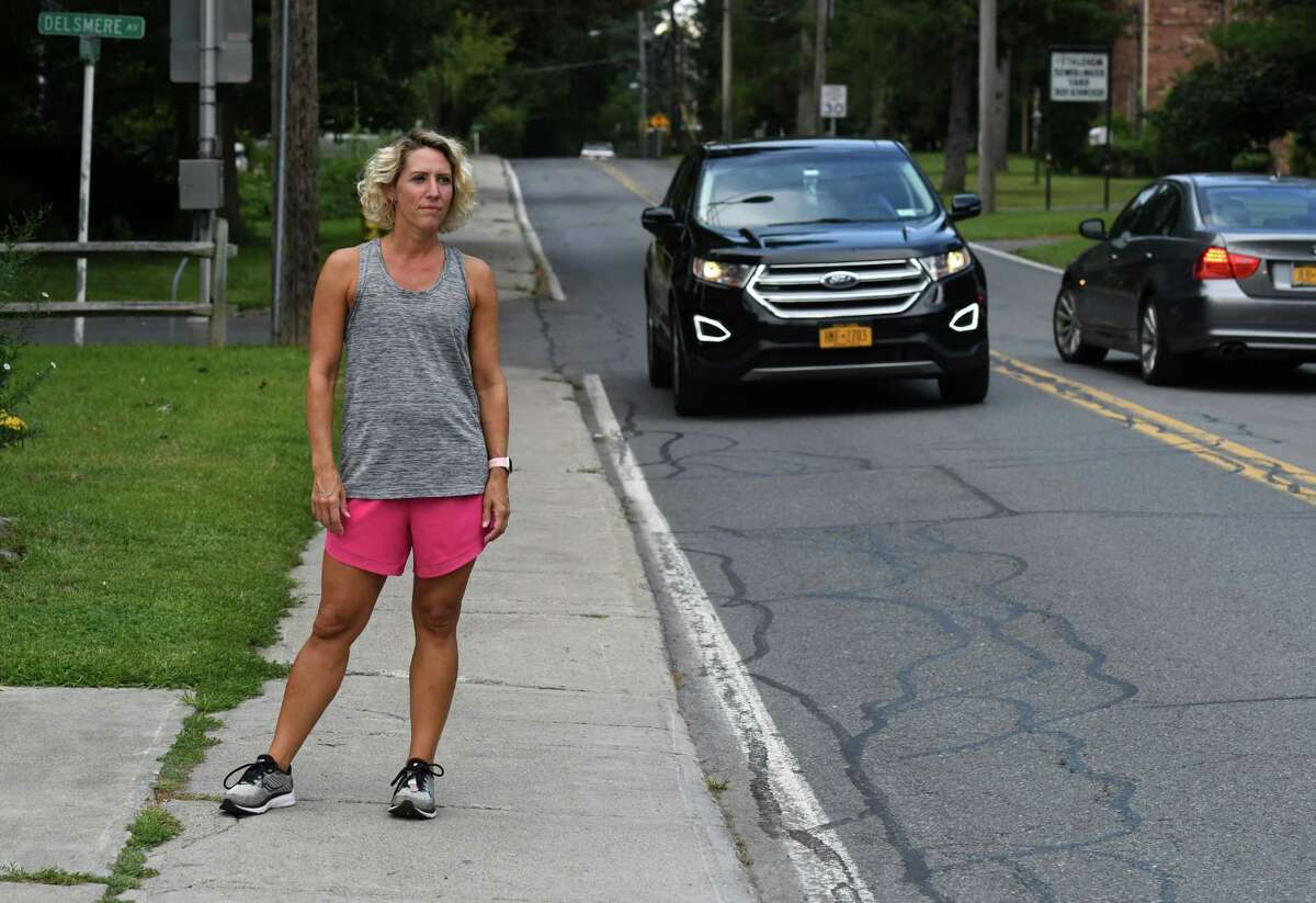 Jen Hebner stands on the sidewalk on Kenwood Avenue where she was hit in the back of the head by a truck's door mirror while running last week on Monday, Aug. 30, 2021, in Delmar, N.Y. She is urging the town to put in temporary safety measures outside nearby Bethlehem Middle School.