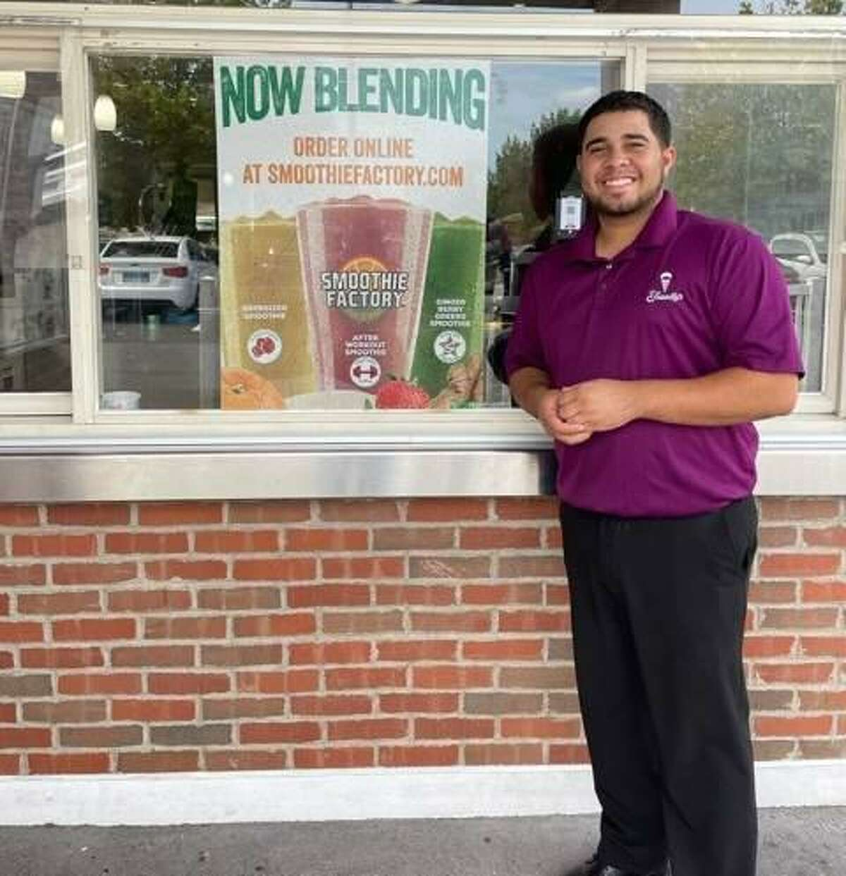 Wilbert Vidro, general manger of the North Haven Friendly's, stands next to a sign advertising vegetable and fruit smoothies as the latest menu edition.