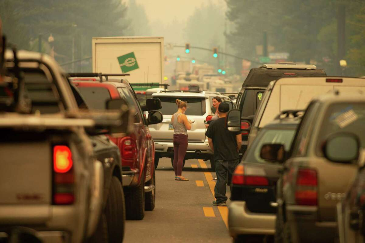 South Lake Tahoe residents mill around their vehicles while they are all stuck in eastbound evacuation traffic on Highway 50 after mandatory evacuation orders were issued to all of South Lake Tahoe, Calif. due to the approaching Caldor Fire, on Monday, Aug. 30, 2021.