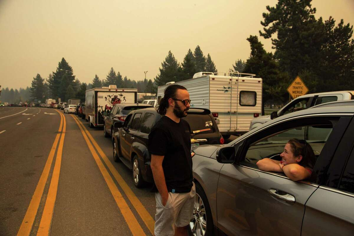Shawn Hoffman, left, talks with his partner Madison Sites while they wait in eastbound evacuation traffic on Highway 50 after mandatory evacuation orders were issued to all of South Lake Tahoe, Calif. due to the approaching Caldor Fire, on Monday, Aug. 30, 2021.