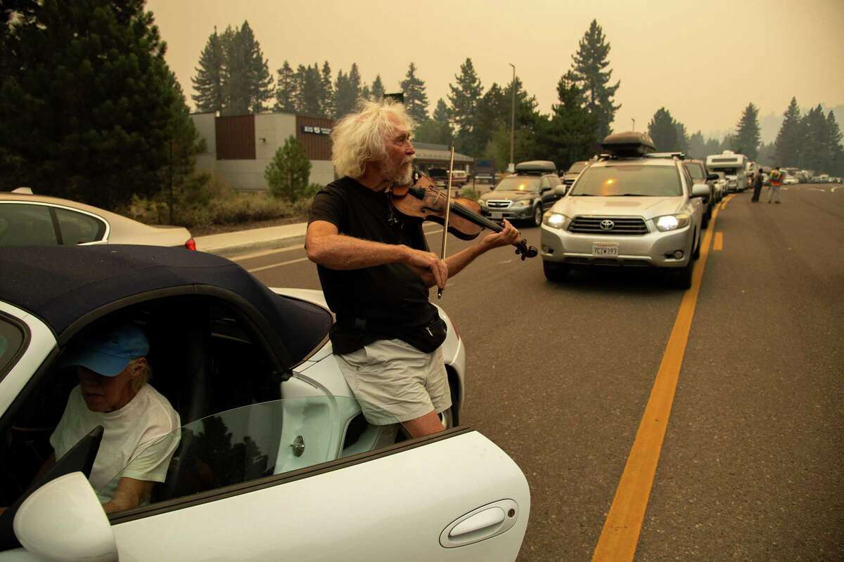 Longtime Tahoe area resident Mel Smothers leans against his wife Liz Hansen's car and plays his violin while they are stuck in two hours of eastbound evacuation traffic on Highway 50 after mandatory evacuation orders were issued to all of South Lake Tahoe, Calif. due to the approaching Caldor Fire, on Monday, Aug. 30, 2021.