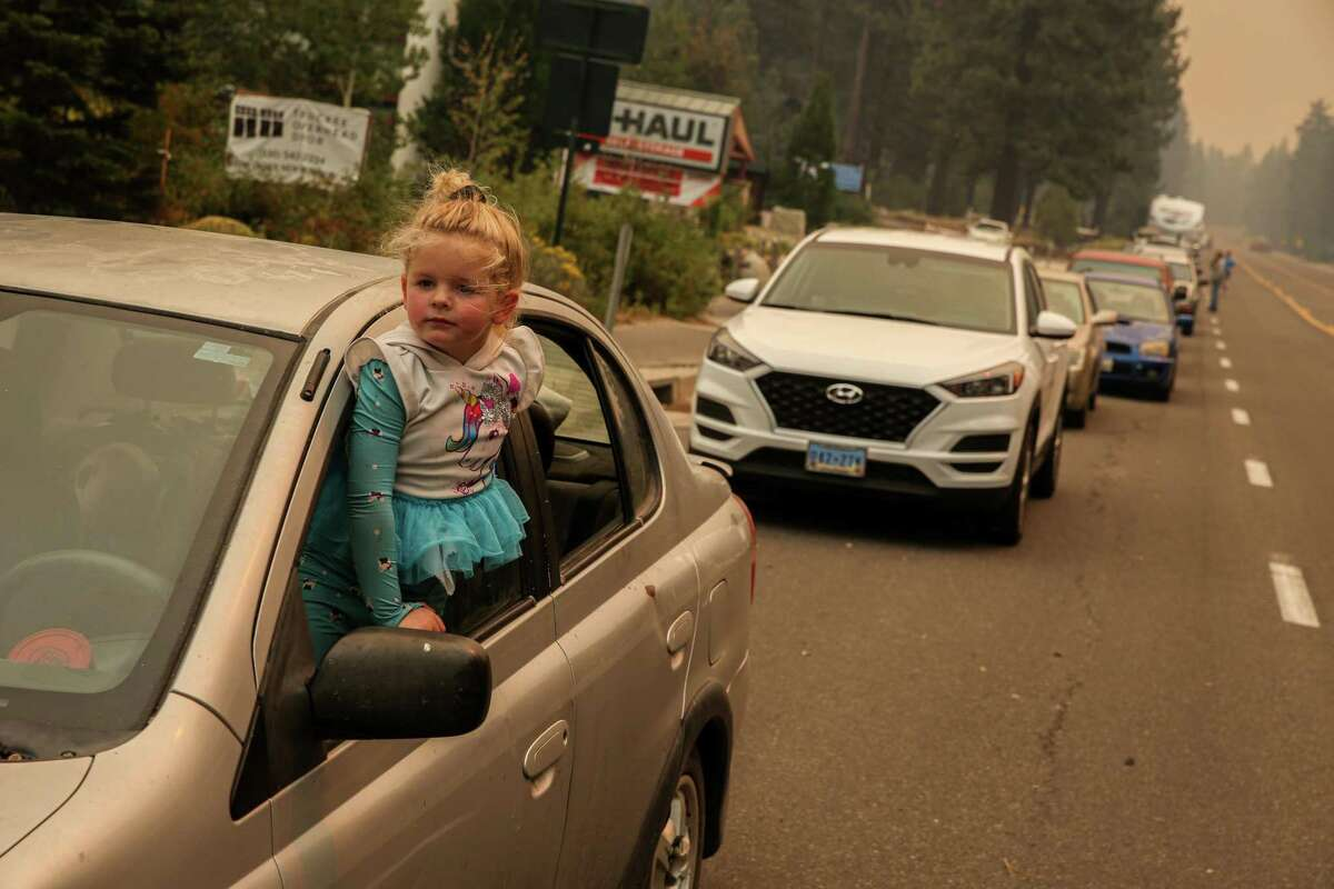 Three-year-old Madeleine Castellanos and her mother wait in an evacuation line on Highway 50 in South Lake Tahoe on Monday due to the threat of encroaching wildfire flames from the Caldor Fire.