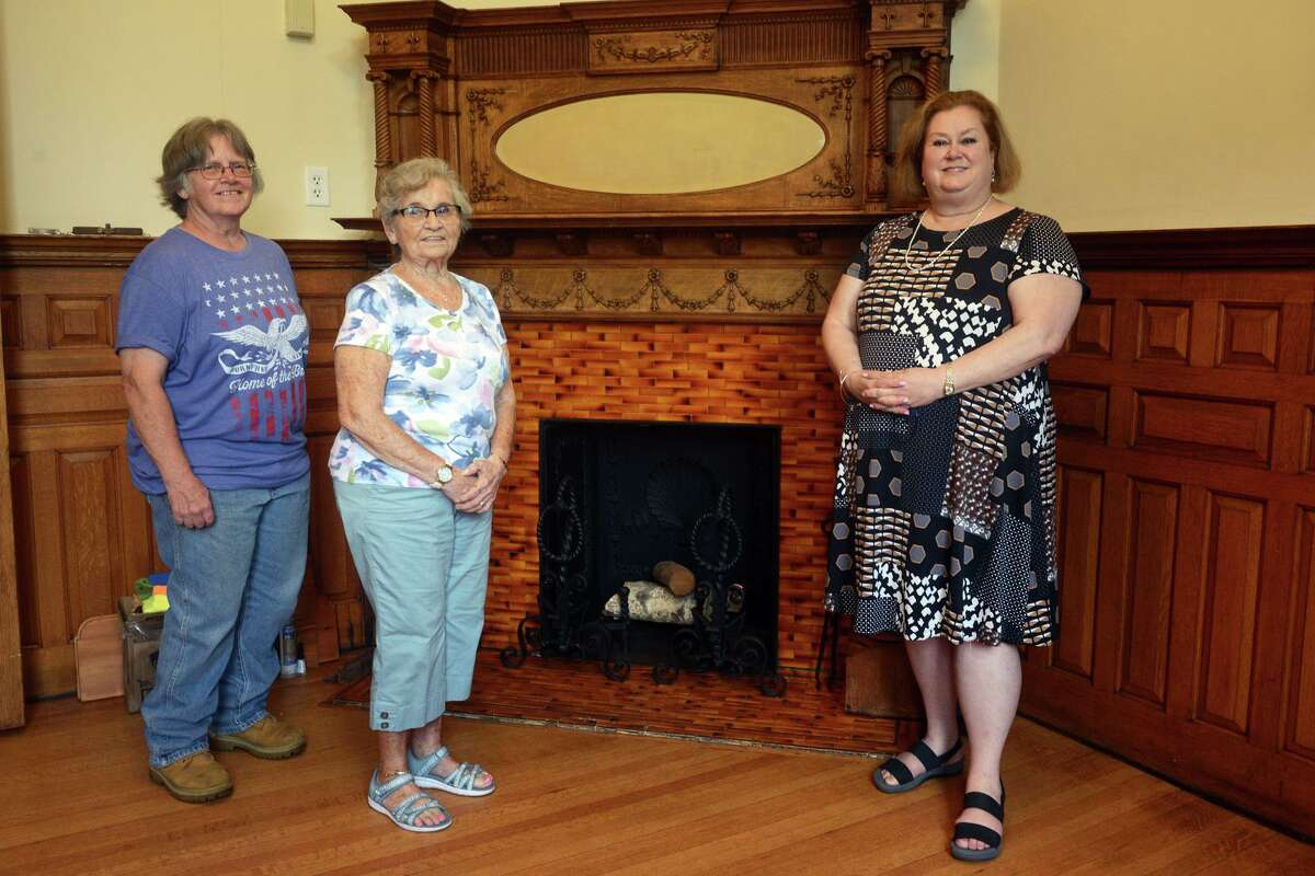 Library director Joan Stokes, right, poses with volunteers Kyna Lesko, left, and Nancy Wilmink, center, near a fireplace in the original section of Plumb Memorial Library, in Shelton, Conn. Aug. 27, 2021. Completed in 1895, the library is currently under renovations that will highlight its original architectural splendor.