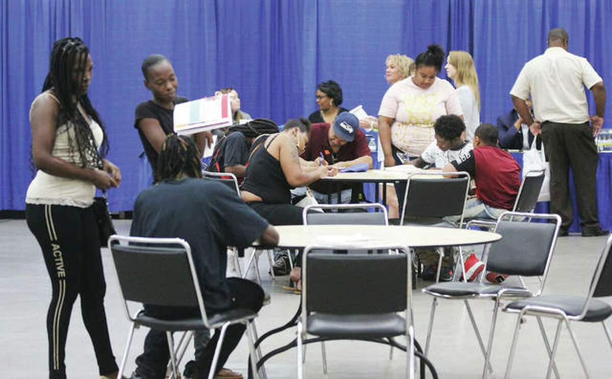 FILE - Job seekers talk and work on applications at Jobs Plus '19, the annual job fair sponsored by Madison County Employment and Training and the St. Clair County Intergovernmental Grants Department.