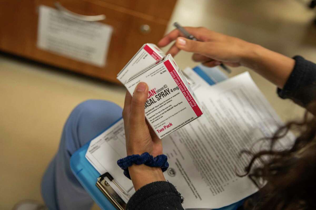 Rachel Perera, a patient navigator with the Addiction Care Team at San Francisco General Hospital, checks on two boxes of Narcan nasal spray as she gathers supplies, a harm reduction strategy, for a patient in the process of being discharged in San Francisco, July 14, 2021.