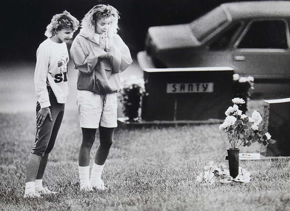 Kristy Webb (left) and Bev Lehr, then teenagers, visit the unmarked grave of Heather Sims in Woodland Hill Cemetery in Wood River. The killing of the girl grabbed the attention of many people who visited the grave in 1989.