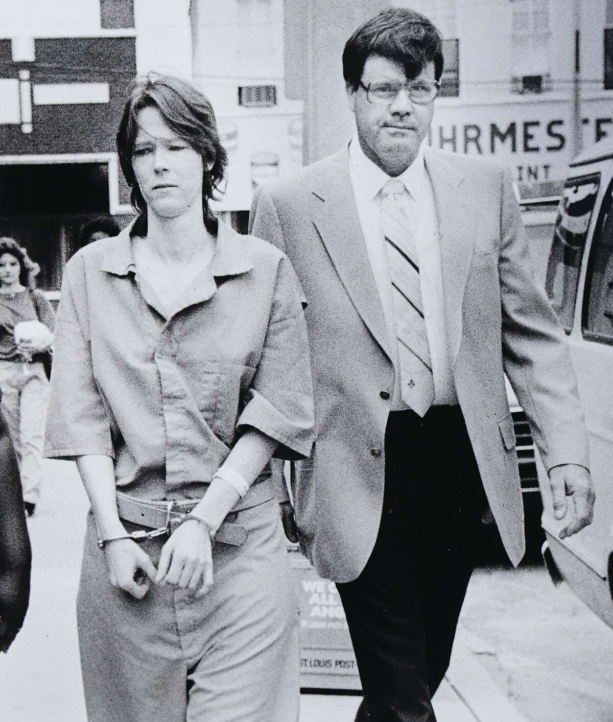 Wearing standard jail clothing, Paula Sims is escorted by a sheriff's deputy at Madison County Courthouse.