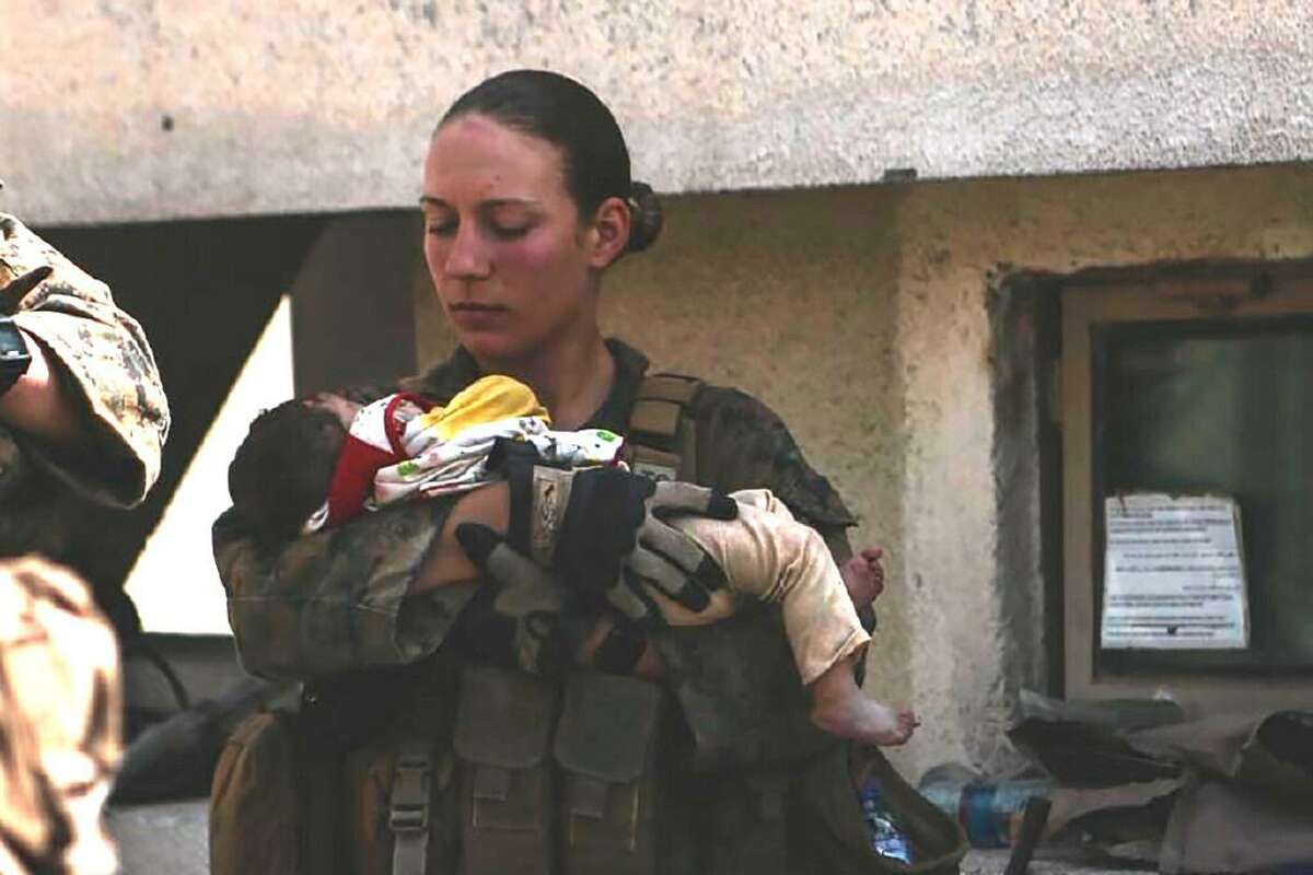 Sgt. Nicole Gee of Sacramento, shown holding a baby at Hamid Karzai International Airport in Kabul in a photo posted Aug. 20 on Twitter, was killed in Thursday's bombing in Kabul.