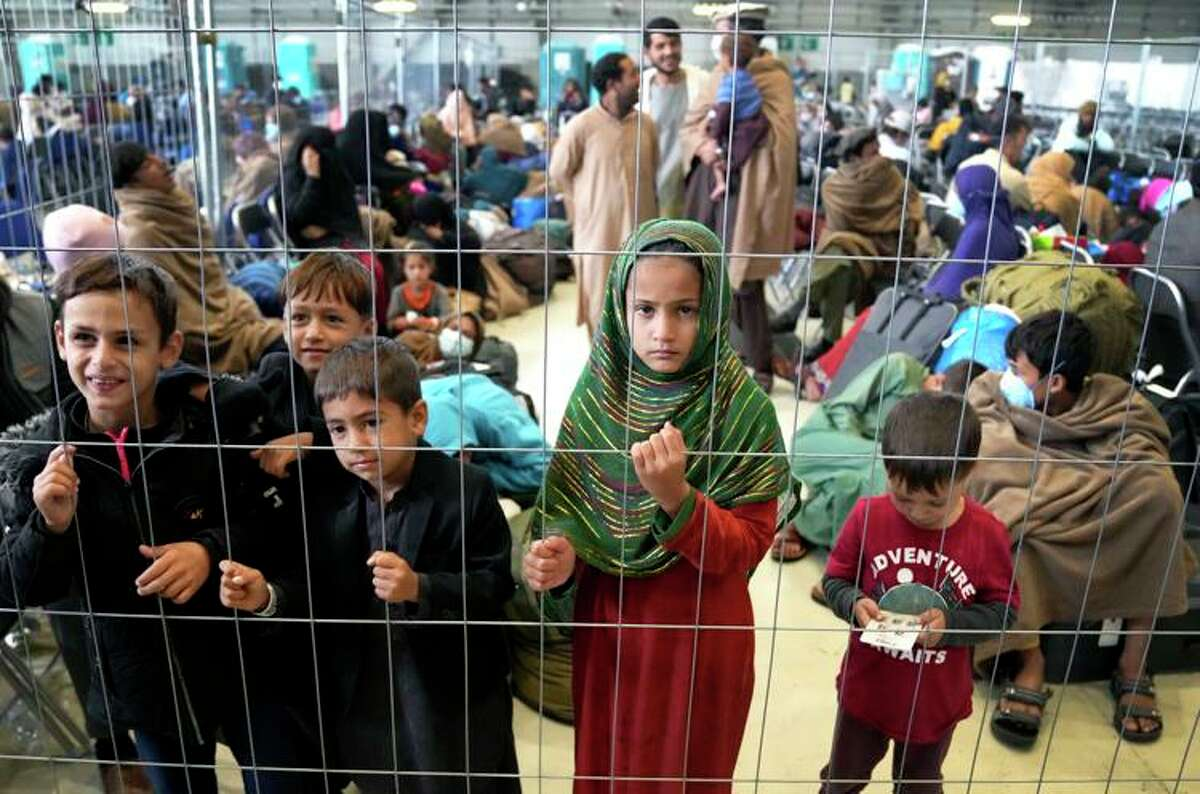 Children stand behind a fence in a hangar Monday as they wait for their departure at Ramstein U.S. Air Base in Ramstein, Germany. The largest American military community overseas now houses thousands of Afghan evacuees in a tent city at the airbase.