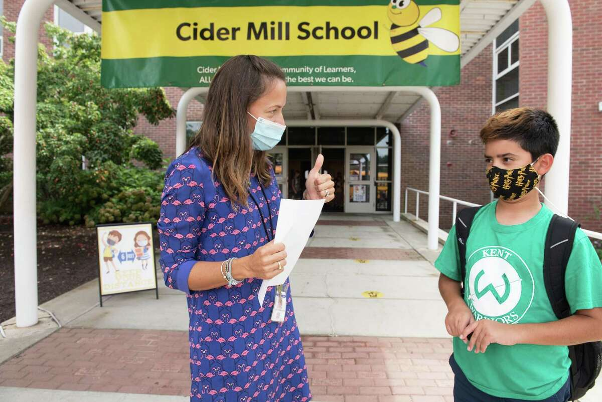 Katie Froehlich helps Cider Mill Students head to their buses after the first day of school on Monday, August 30, 2021 in Wilton, Connecticut