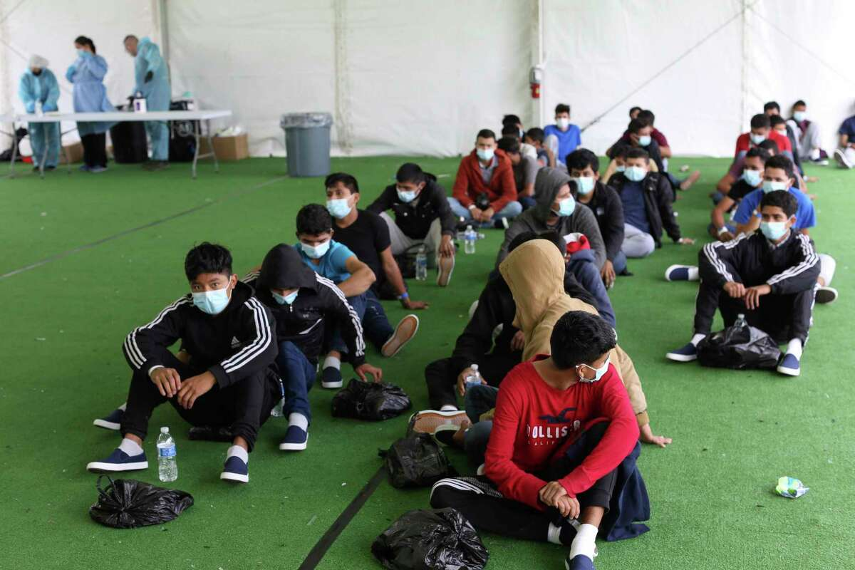 In this March 30, 2021 file photo, young migrants wait to be tested for COVID-19 at the Donna Department of Homeland Security holding facility, the main detention center for unaccompanied children in the Rio Grande Valley, in Donna, Texas.