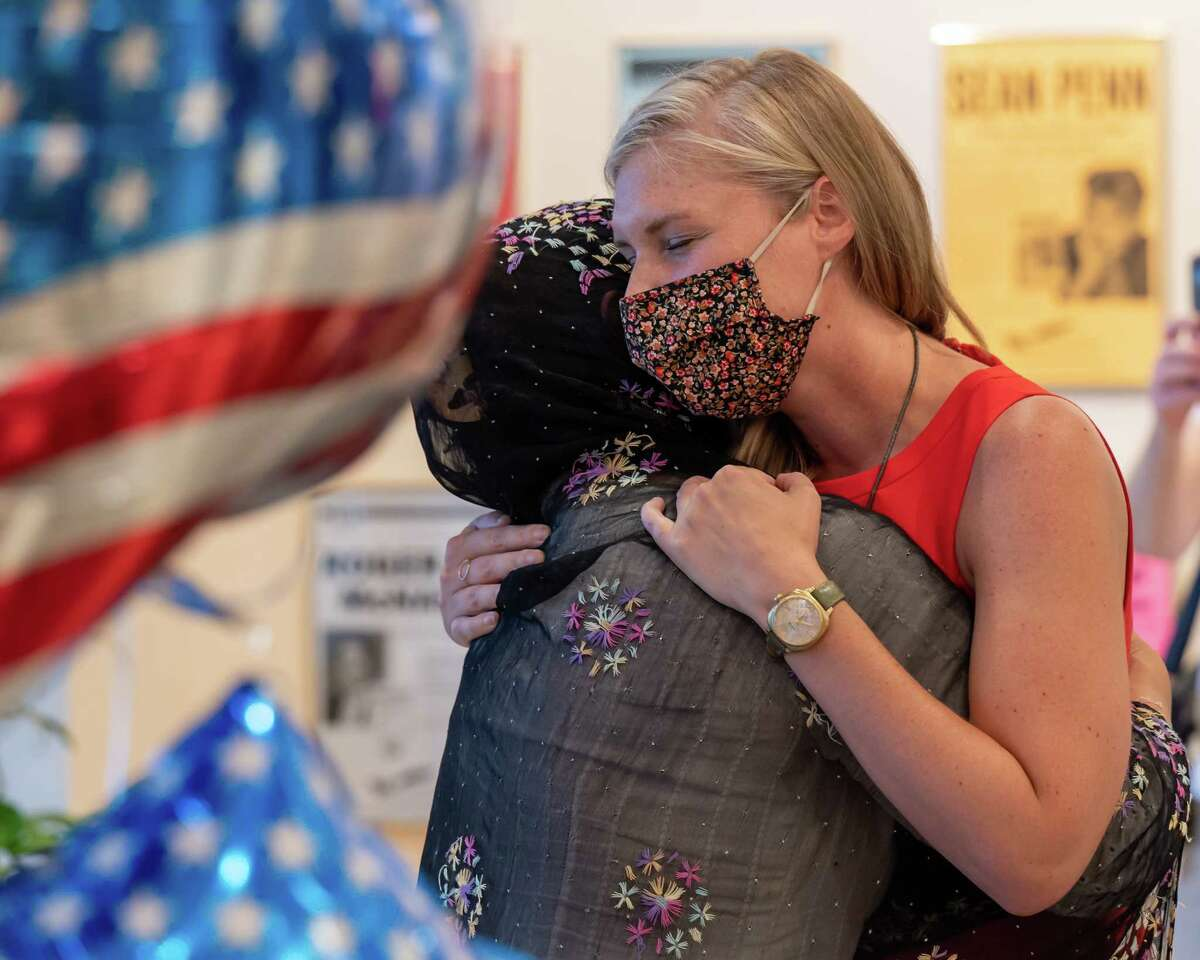 Sara Lowry, a staff attorney for the U.S. Committee for Refugees and Immigrants, hugs Suneeta, the Capital District-based mom who fled the terror in Afghanistan, at the Albany International Airport. The children were stuck in their native country but recently flew into Washington DC and then into Albany on Monday, Aug. 30, 2021. Gov. Kathy Hochul announced Thursday that over 1,000 Afghan refugees are expected to settle in New York in the coming months. (Jim Franco/Special to the Times Union)