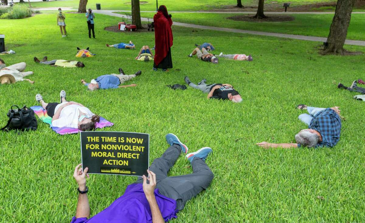 """People participate Monday afternoon, Aug. 30, 2021 in a die-in on the grounds of the Texas capitol during an event organized by the Texas Poor People's Campaign to protest the """"carelessness of our elected officials,"""" according to a press release sent out by the group. The group says the event was the start of a series of they are calling Moral Mondays."""