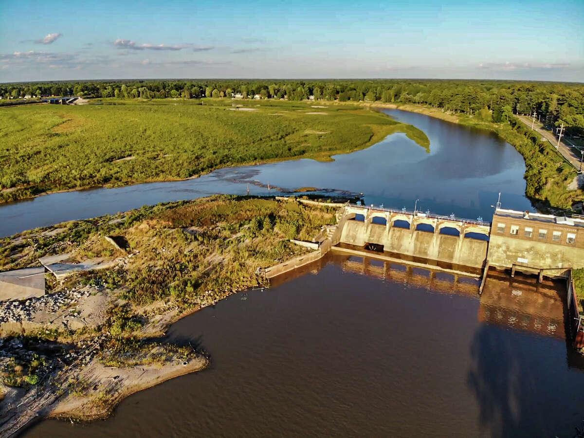 The sun sets over the Sanford Dam Monday, Aug. 30, 2021. (Adam Ferman/for the Daily News)