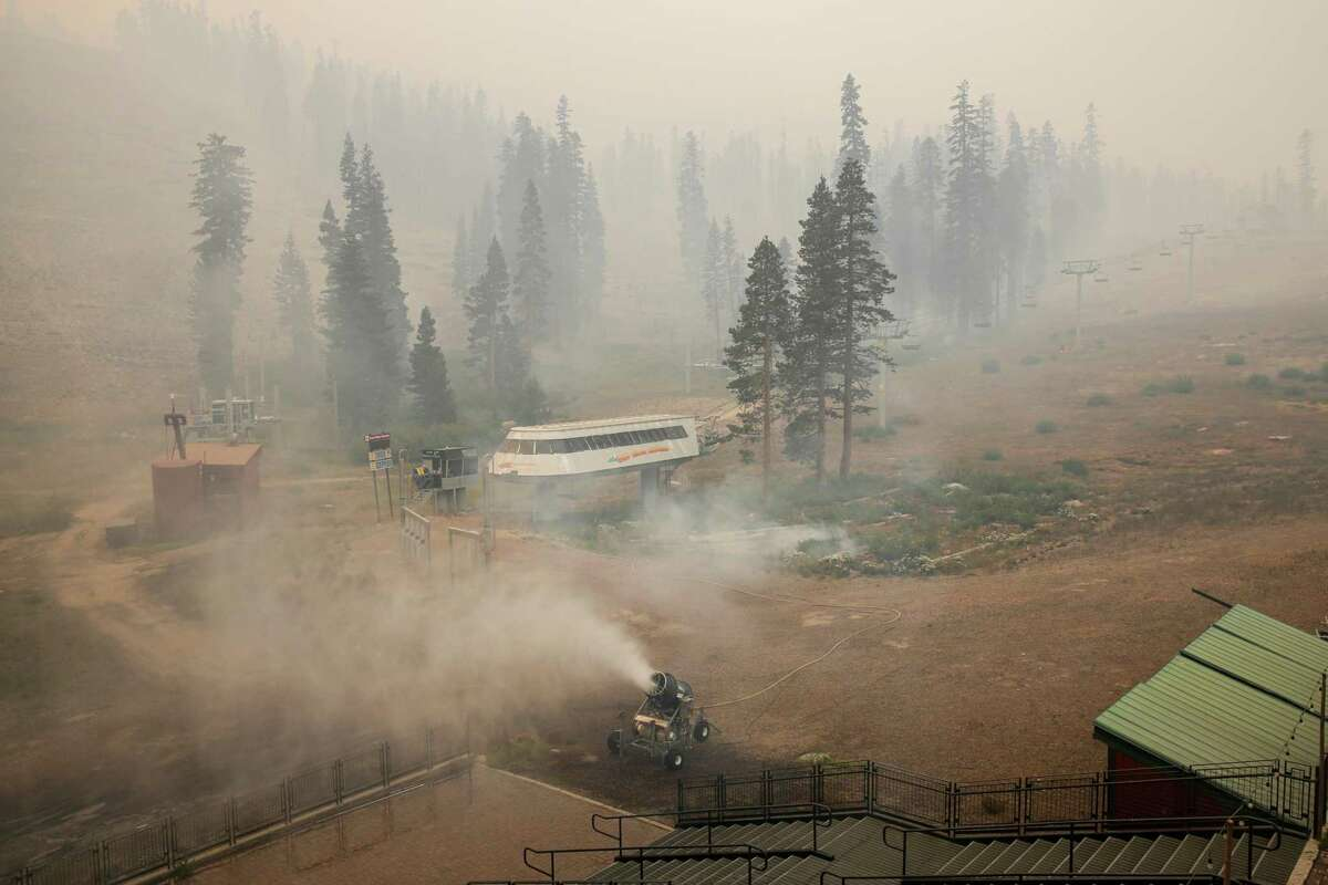 A snow maker drenches a slope-facing patio in efforts to protect it from the Caldor Fire at Sierra-at-Tahoe ski resort.