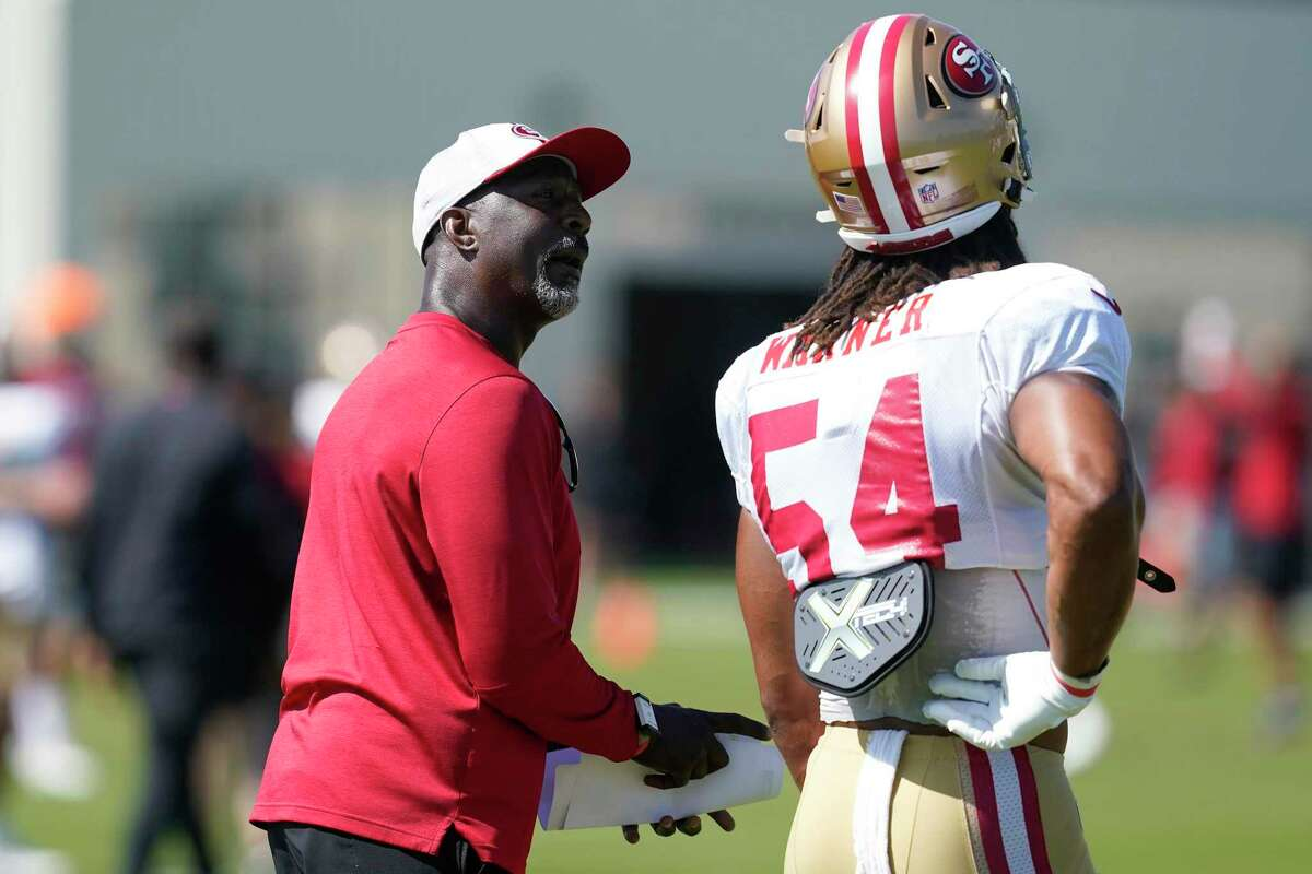 San Francisco 49ers linebackers coach Johnny Holland, left, talks with middle linebacker Fred Warner (54) at NFL football training camp in Santa Clara, Calif., Tuesday, Aug. 10, 2021. (AP Photo/Jeff Chiu)