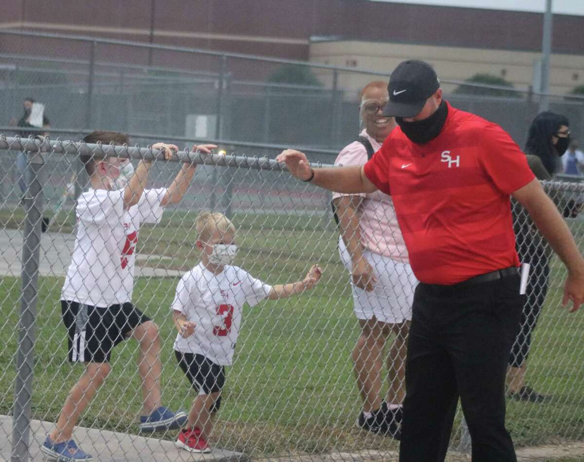 """South Houston head football coach Patrick Longstreet says hello to his children before last year's Santa Fe game. When the Trojans and Indians meet again in two weeks, he doesn't want to be """"kidding"""" around, hoping to have his team's nicks and bruises healed, creating a 100 percent healthy roster."""
