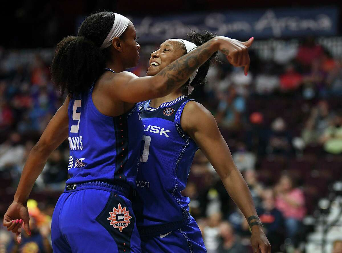 Connecticut Sun's Jasmine Thomas (5) and Briann January (20) celebrate a foul during the team's WNBA basketball game against the Minnesota Lynx on Tuesday, Aug. 17, 2021, in Uncasville, Conn.